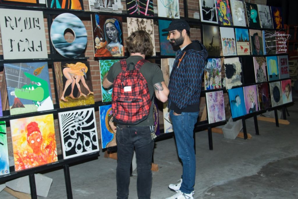 Two people discussing paintings on display
